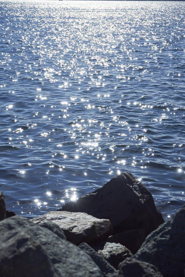 De zonfonkelingen dansen op blauw water royalty-vrije stock afbeelding