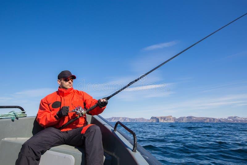 De zonnebril die van de visserssportman in het overzees vissen In de handen royalty-vrije stock afbeelding