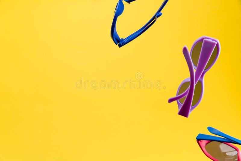 De zonnebril van kleurenkinderen op gele achtergrond wordt geïsoleerd die Concept de zomer en de vakantie van de zonbescherming D stock afbeelding