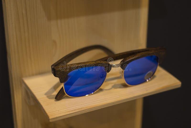 De zonnebril winkelt met houten kaders in modieus in nieuw ontwerp op natuurlijk houten rek stock foto