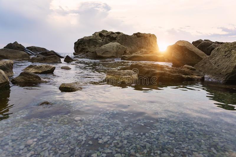 De zonnenstralen bij zonsonderganglicht omhoog de rotsen op de kust van de Zwarte Zee Het strand van kinderen in Alupka stock afbeeldingen