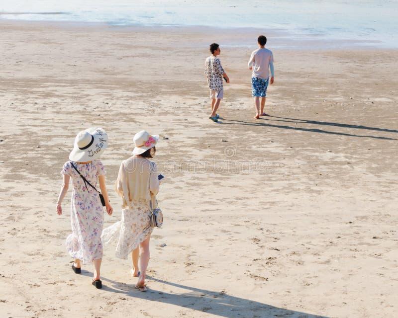 De zonnige dag, de achtermening van twee jonge vrouwen in lange kleding en de hoeden wandelen langs zandig strand stock foto