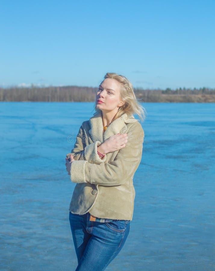 De zonnige dag op het ijs van meer loopt een mooi meisje royalty-vrije stock fotografie