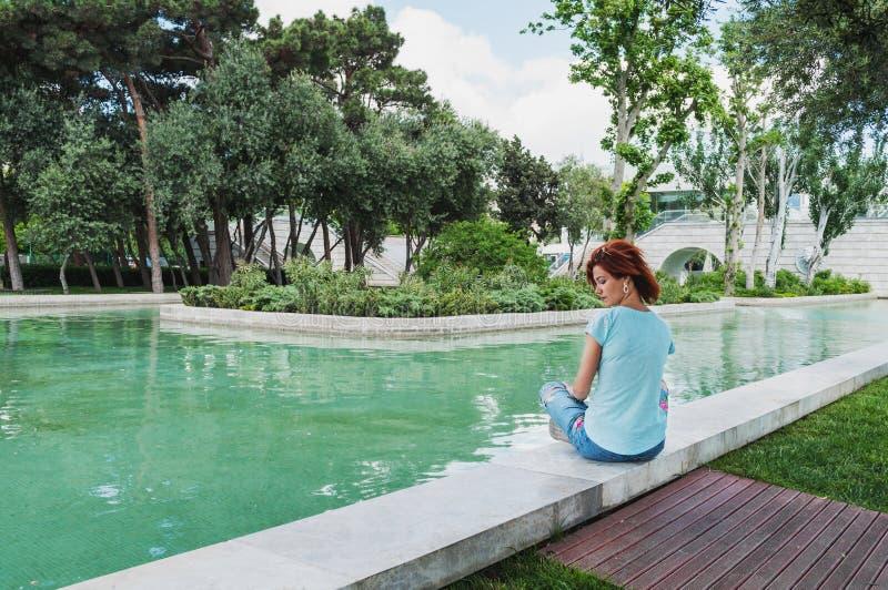 De zonnige dag van de zomer De jonge vrouw zit buiten op kust van het kanaal Meisje die na training rusten stock fotografie