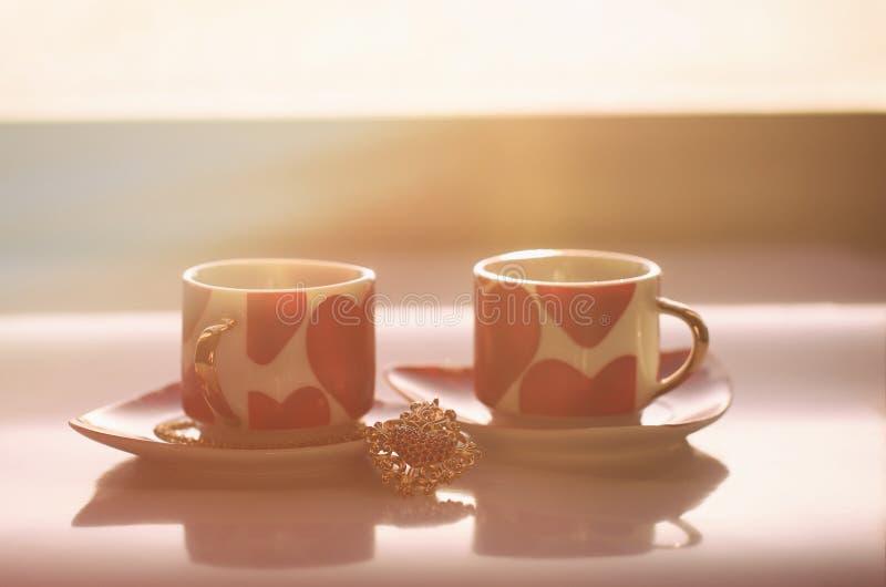 De zonnige ochtend van de dag van Valentine ` s begint met twee die mokken met harten worden verfraaid royalty-vrije stock fotografie