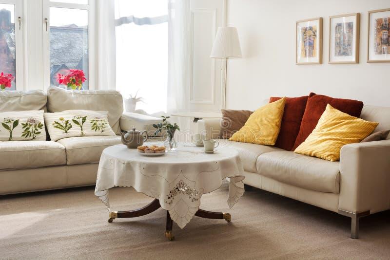 De zonovergoten klassieke stijlwoonkamer met twee leerbanken en de thee dienden op een kleine rondetafel stock fotografie
