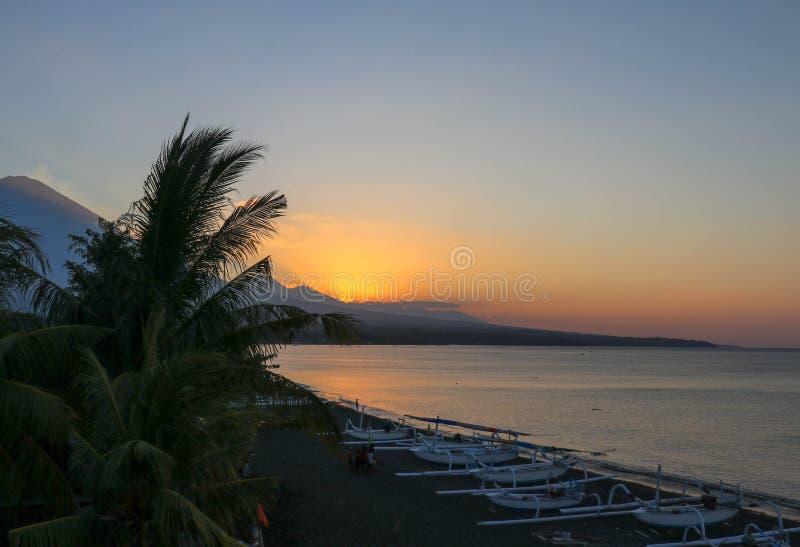 De zonreeksen achter een bergketen dichtbij de actieve vulkaan op het Eiland van Bali De hemel bevlekte sinaasappel van de het to stock fotografie