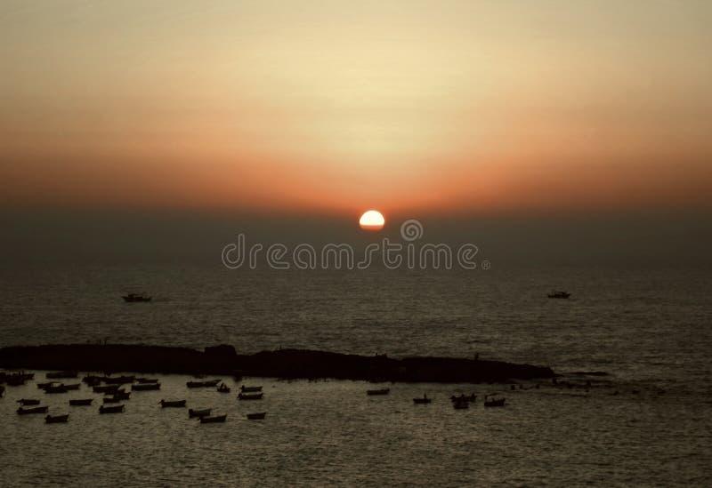 De zonreeksen over de de vissenboten en vissers bij de kust van Alexandrië, Egypte stock afbeeldingen