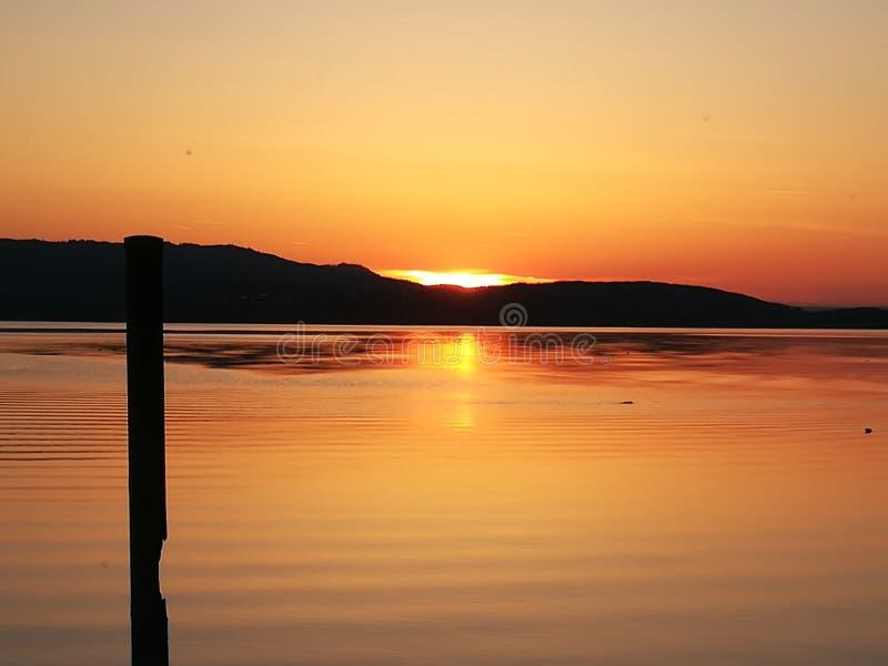 De zonsondergang bij ziet met bergen royalty-vrije stock fotografie