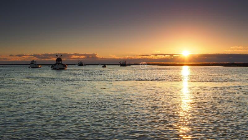 De zonsondergang die in het overzees met kleine vissersboten nadenken verankerde in kalm water, Orford, Suffolk stock afbeelding