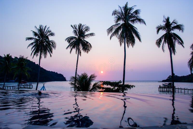 De zonsondergang die de waterspiegelvoorgrond met ao van het kokospalmengebied klapbao bij Koh kood eiland overdenken is een dist stock afbeeldingen