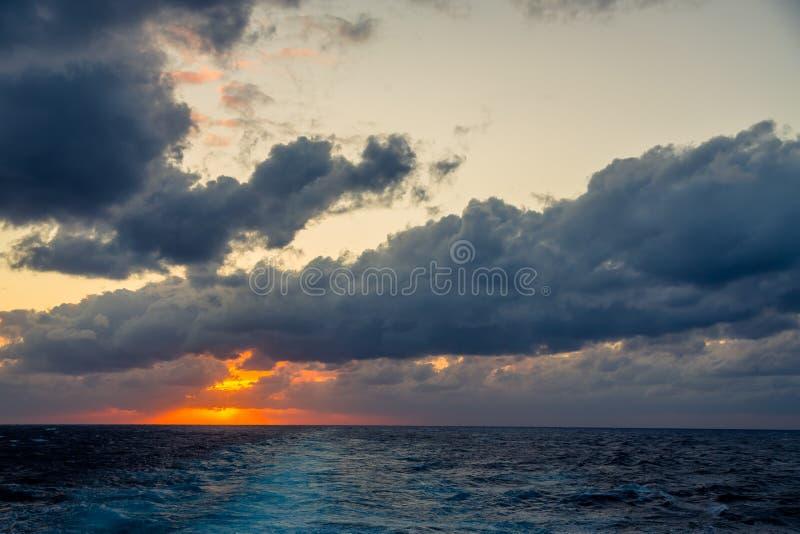 De zonsondergang en de dramatische reeks wolken die over de tropische wateren van de Caraïbische Zee afdrijven worden aangestoken royalty-vrije stock fotografie