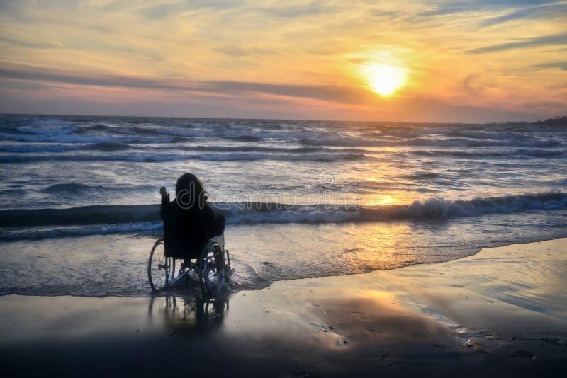 De zonsondergang, maakt het sightseeing van op het strand een vrouw op een rolstoel stock afbeeldingen