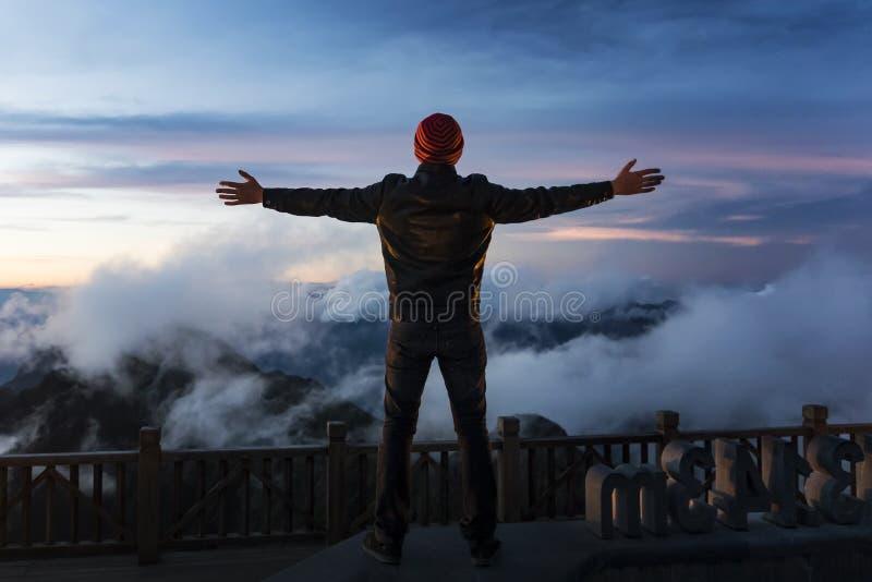 De zonsondergang op Fansipan, Silhouet van de mens bevindt zich bovenop berg en het uitspreiden hand v??r zonsopgang Emotionele s stock fotografie