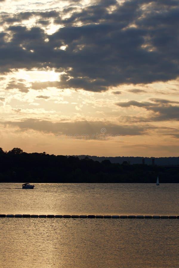 De zonsondergang op het meer met twee jachten stock afbeeldingen