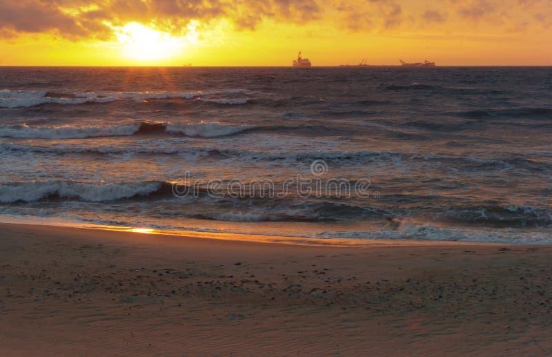 De zonsondergang op het overzees, de golven sloeg tegen de golfbreker, het overzees bij dageraad, de schepen op de horizon royalty-vrije stock foto's