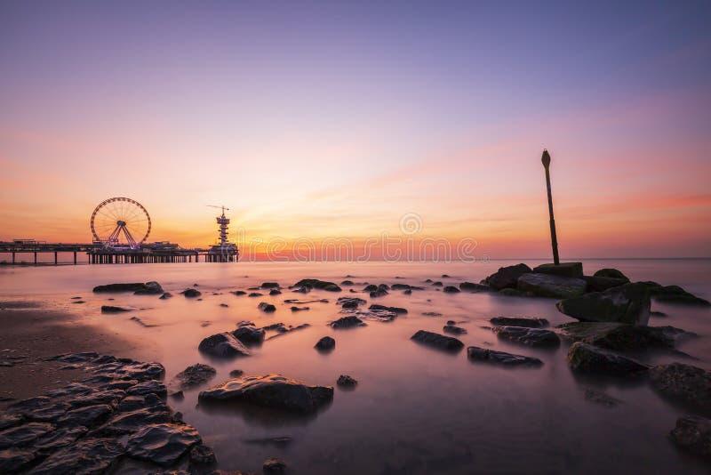 de zonsondergang op kustlijn, het strand, de pijler en ferris rijden, Scheveningen, Den Haag stock afbeeldingen