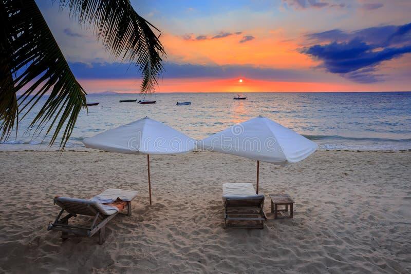 De zonsondergang over Bemoeiziek Madagascar is strand met sunlounger royalty-vrije stock afbeelding