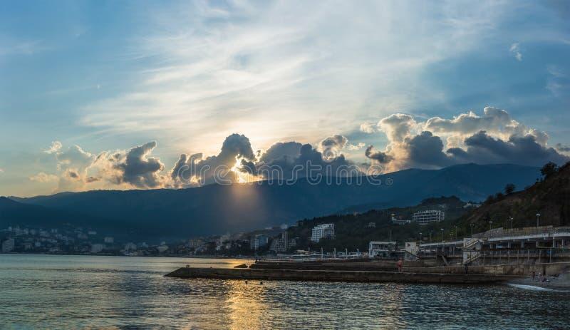 De zonsondergang over de bergen en de Zwarte Zee in de Krim stock foto's