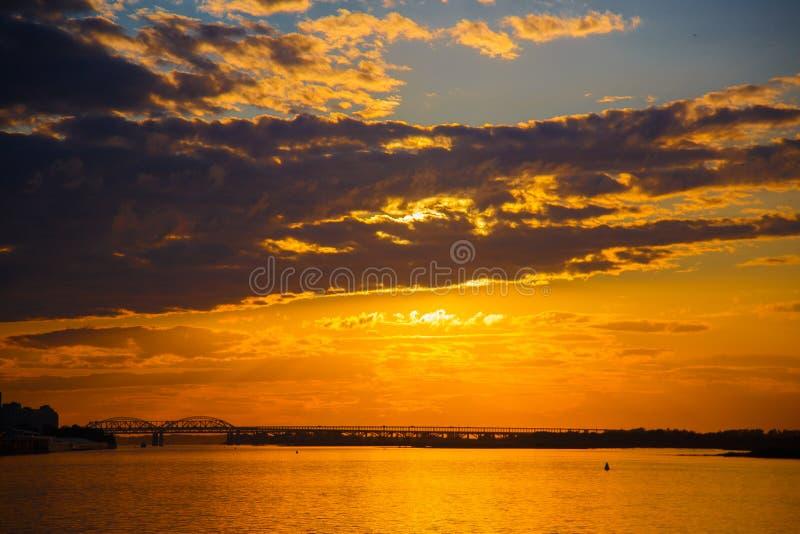 De zonsondergang over de rivierhemel betrekt landschap De zonsondergang van de avond stock fotografie