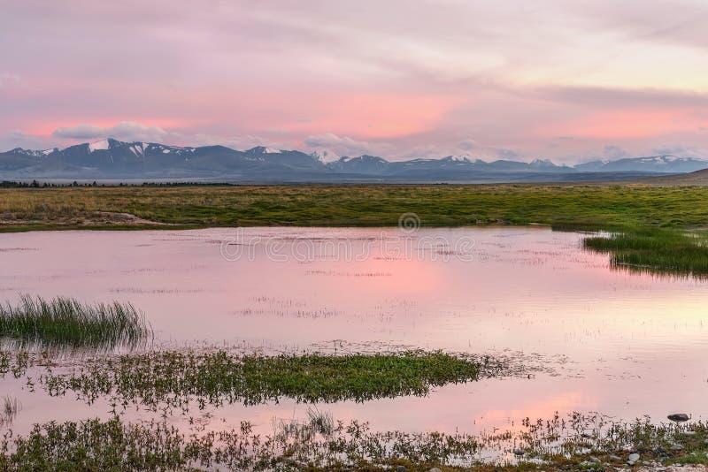 De zonsondergang roze wolken van meerbergen stock afbeeldingen