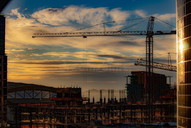 De zonsondergang van de binnenstad over bouwwerf met kraan royalty-vrije stock afbeelding