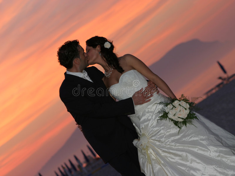 De zonsondergang van de bruidegom en van de bruid het kussen stock foto's