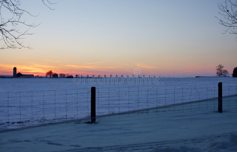 De Zonsondergang van de winter op het Landbouwbedrijf royalty-vrije stock afbeelding