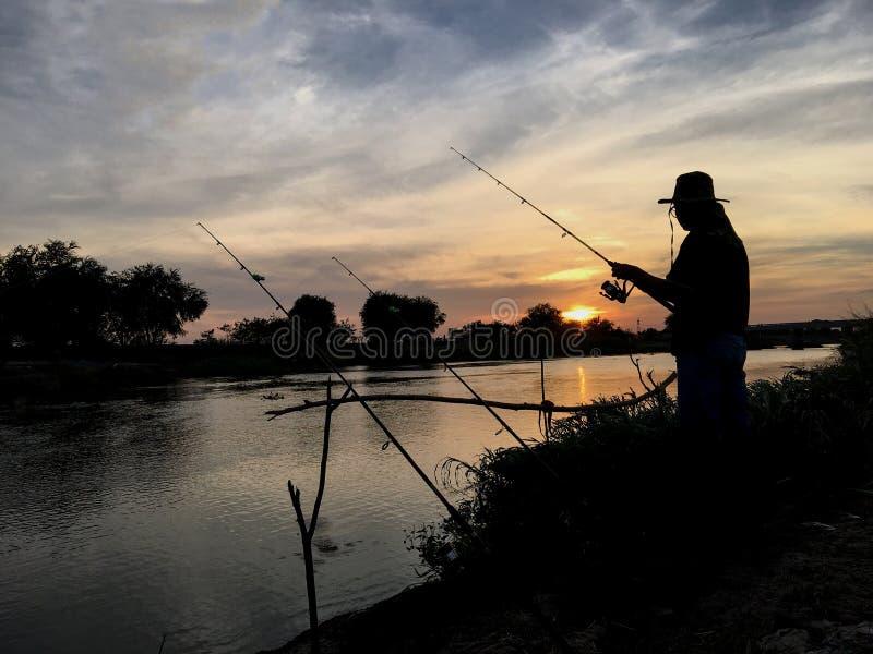 De zonsondergang van het visserssilhouet royalty-vrije stock foto's