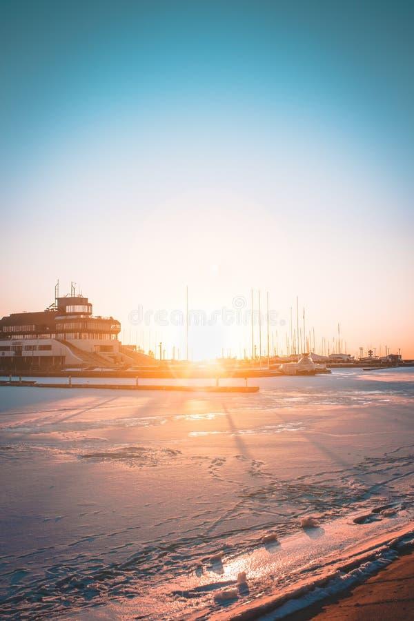 De zonsondergang van de jachthaven door het overzees stock foto