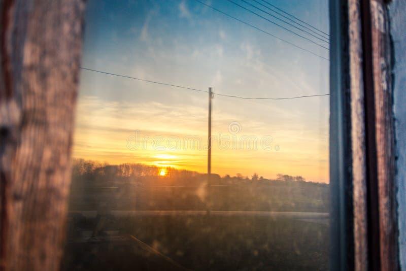 De zonsondergang wordt weerspiegeld in oud huisvenster royalty-vrije stock afbeelding