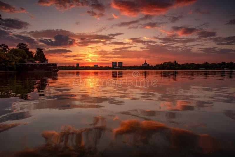 De zonsondergangcityscape van Boekarest in Herastrau-park in de herfsttijd September stock afbeeldingen