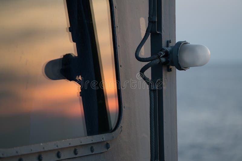 De zonsonderganghemel overdenkt de marine schip` s venster royalty-vrije stock fotografie