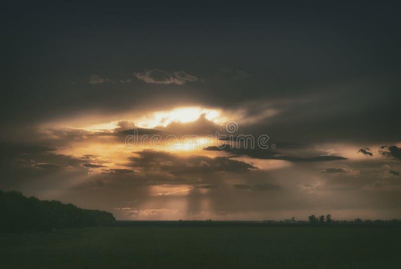 De zonsondergangstralen van de zon maken hun manier door de avondwolken royalty-vrije stock foto