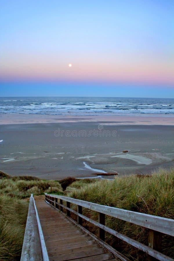 De zonsopgang en de maan van het strand stock foto