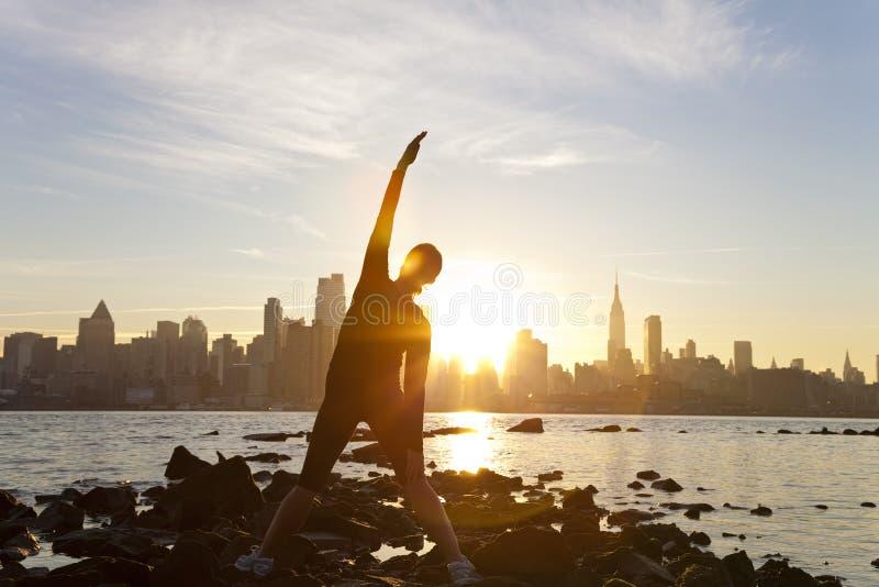 De Zonsopgang New York van de Horizon van Manhattan van de Yoga van de vrouw stock afbeeldingen