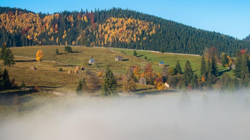 De zonsopganglandschap van de Bucovinaherfst in Roemenië met mist en bergen royalty-vrije stock afbeelding