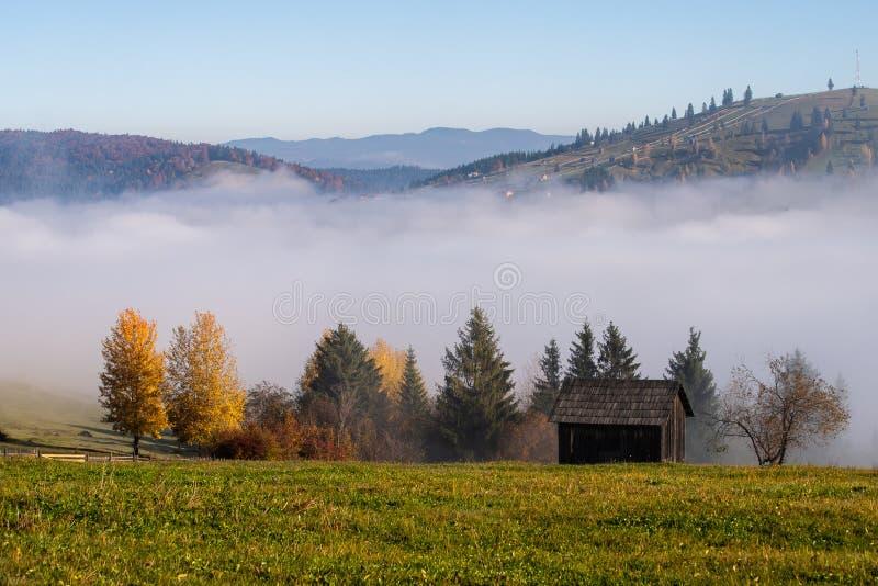 De zonsopganglandschap van de Bucovinaherfst in Roemenië met mist en bergen royalty-vrije stock fotografie