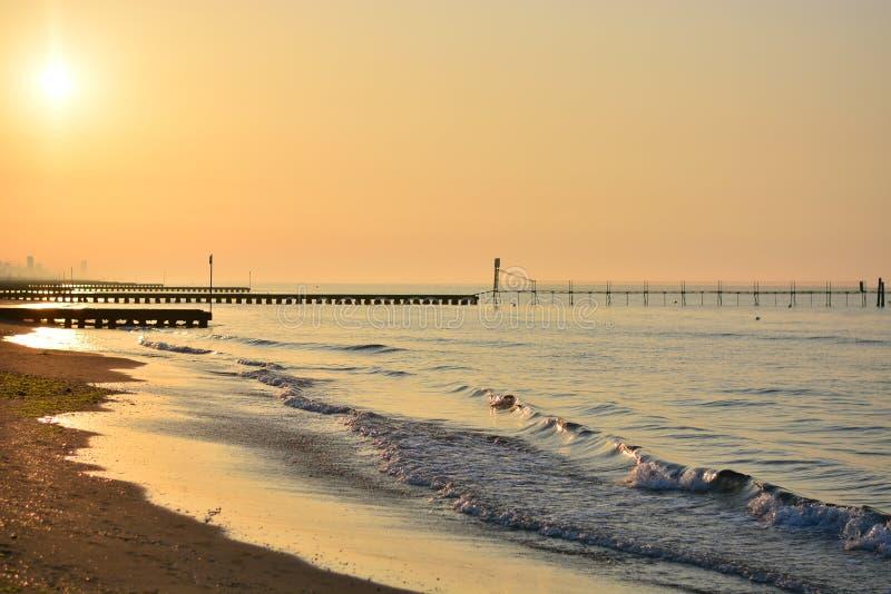 de zonstijgingen op het overzees en van een schitterende mening met een pier die de horizon bereikt stock foto