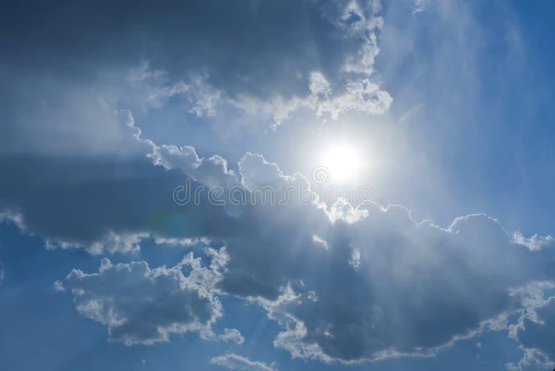 De zonstralen door de wolk stock fotografie
