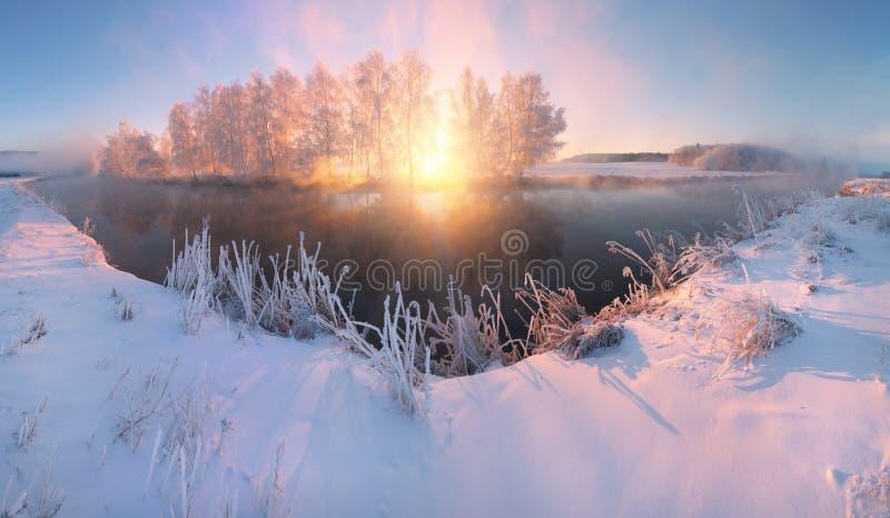 De zonstralen verlichten sneeuwrivieroever stock afbeeldingen