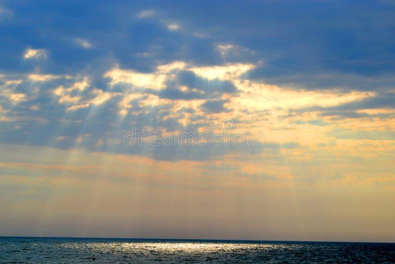De zonstralen verwarmen het overzees zelfs door de wolken royalty-vrije stock afbeelding