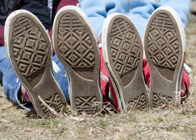 De zool van de bodem van tienertennisschoenen buiten in gras royalty-vrije stock foto