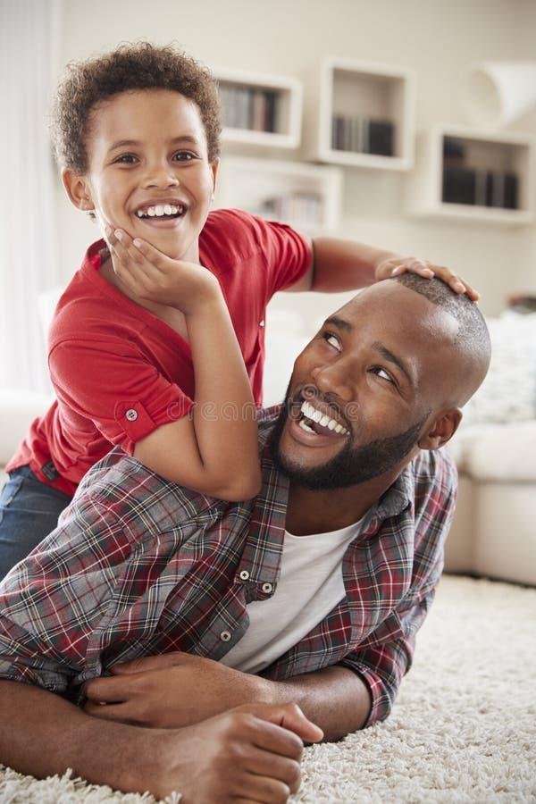 De zoon beklimt op Vaders Achter aangezien zij Spel samen in Zitkamer spelen royalty-vrije stock fotografie