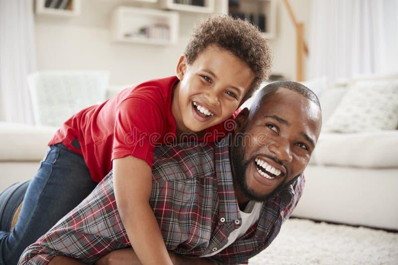 De zoon beklimt op Vaders Achter aangezien zij Spel samen in Zitkamer spelen stock foto's