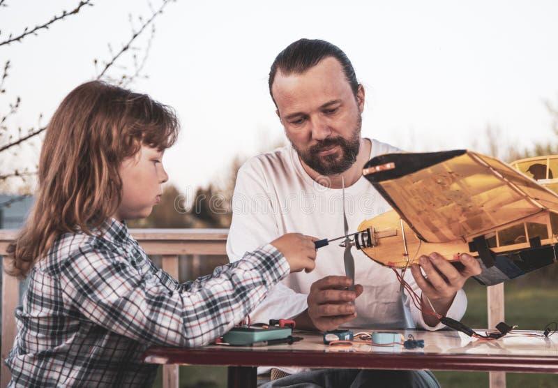 De zoon en het vader gemaakte eigengemaakte radio-gecontroleerde modelvliegtuigenvliegtuig zijn hand - gemaakt niet auteursrecht royalty-vrije stock fotografie