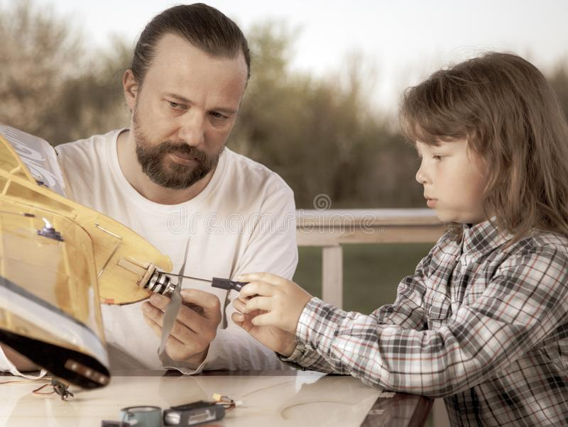 De zoon en het vader gemaakte eigengemaakte radio-gecontroleerde modelvliegtuigenvliegtuig zijn hand - gemaakt niet auteursrecht stock afbeelding