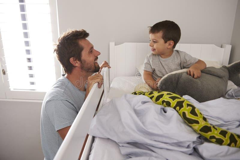 De Zoon van vadersaying goodnight to bij Bedtijd stock afbeelding
