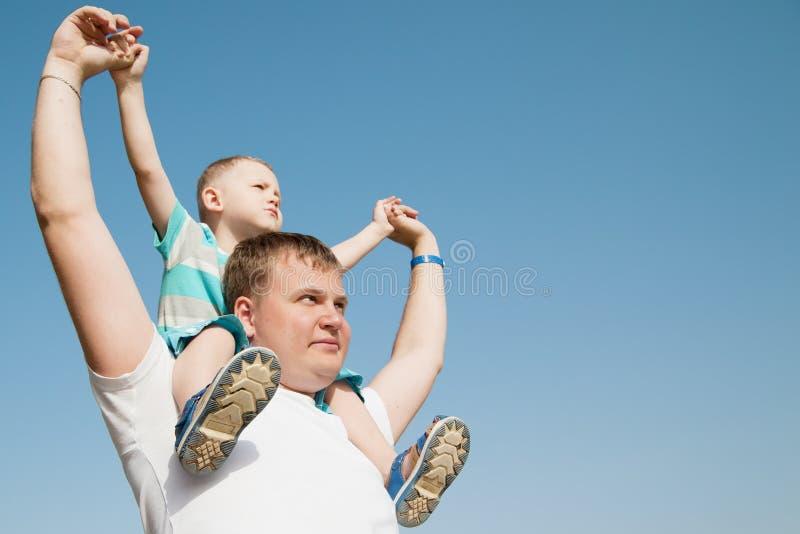 De zoon zit op de schouders van de vader stock afbeeldingen
