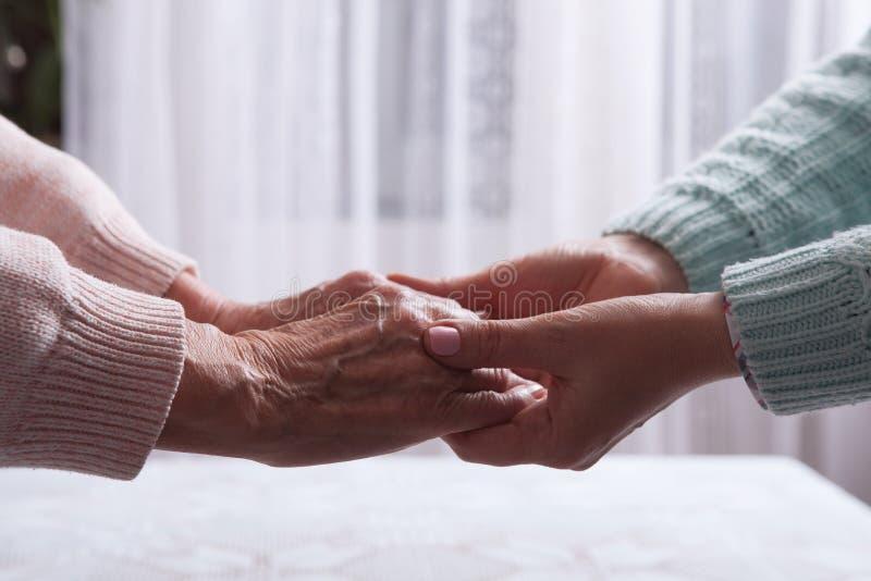 De zorg is thuis van bejaarden Hogere vrouw met hun verzorger thuis Concept gezondheidszorg voor bejaarde oude mensen royalty-vrije stock afbeelding